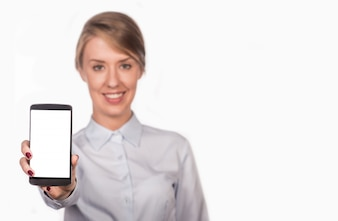 Business woman smiling showing a blank smart phone screen isolated on a white background.Happy pretty woman showing a blank smart phone screen
