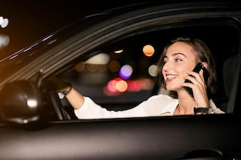 Business woman with the phone in car