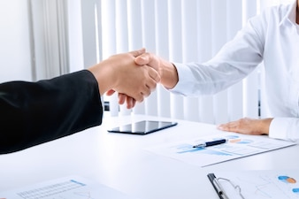 Business women hands shaking at meeting room