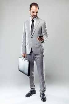 Business young man using his mobile phone over gray background.