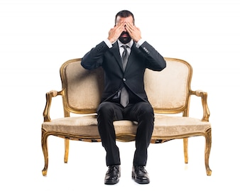 Businessman covering his eyes