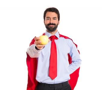 Businessman dressed like superhero holding an apple