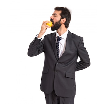 Businessman eating an apple over white