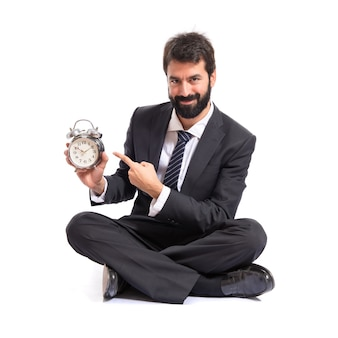 Businessman holding a clock over white background