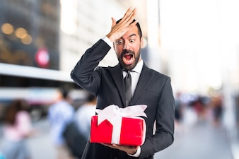 Businessman holding a gift on unfocused background