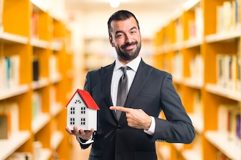 Businessman holding a little house