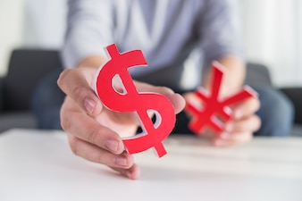 Businessman holding dollar sign and CNY sign