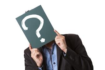 Бизнесмен, проведение зеленый доске, изолированных на белом фоне с рисованием вопросительный знак на доске.