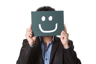 絵を描く笑顔で白い背景に隔離された緑の黒板を持つ実業家黒板に顔文字。