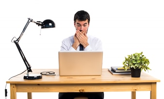 Businessman in his office covering his mouth