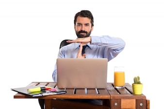 Businessman in his office making time out gesture