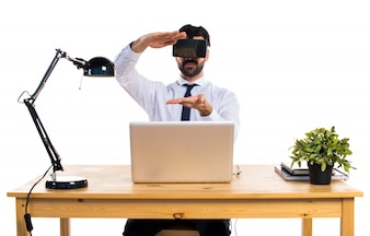 Businessman in his office using VR glasses holding something