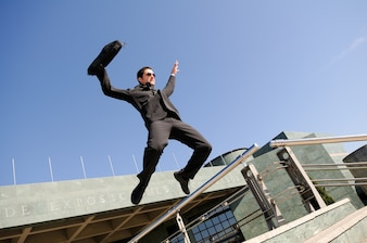Businessman jumping with a briefcase