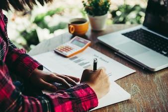 コンピュータのラップトップとの職場会議でノートを作るビジネスマン