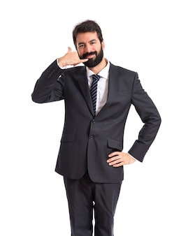 Businessman making phone gesture over white background