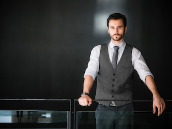 Businessman relax standing on black wall background
