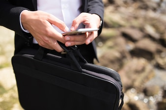 Businessman with briefcase texting message outdoors