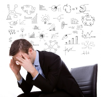 Businessman with hands on head and symbols behind