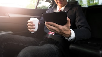 Businessman working in a car and using a tablet while drinking coffee