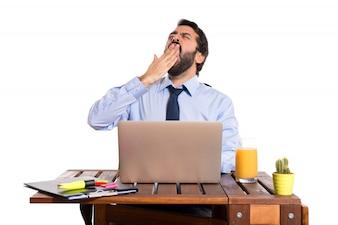 Бизнесмен, зевая в своем офисе