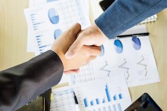 会議中に握手をするビジネスマン