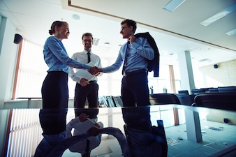 Businesspeople shaking hands at workplace