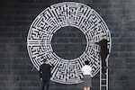 Businesspeople solving a labyrinth