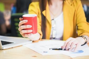 コーヒーブレイク時にコーヒーの赤い杯を保持する実業家。