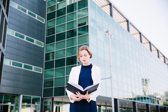 Businesswoman reading in front of building