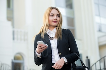 Businesswoman using her smartphone with blurred background