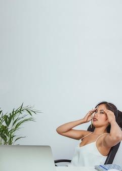 Businesswoman wikth headache after hard work