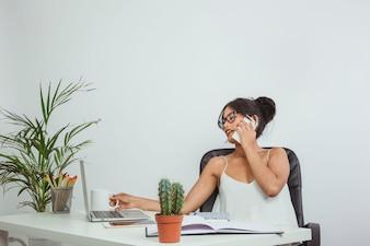 Businesswoman with phone and coffee mug