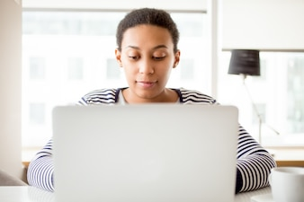 Busy woman using laptop at home