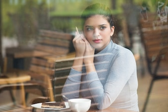 Calm Indian student girl spending leisure in cafe