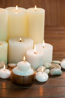 Candles with massage oil bottles and sea salt in wooden bowl