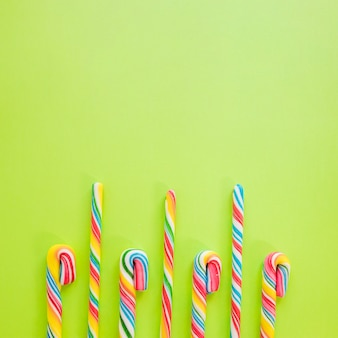 Candy sticks on green background