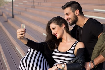 Capturing bright moments. Joyful young loving couple making selfie on camera while standing outdoors.