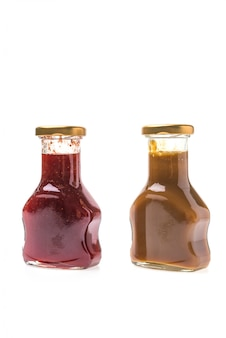 Caramel sauce and strawberry jam bottles