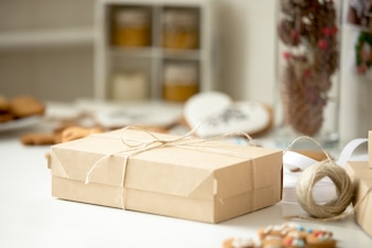 Cardboard box, postal parcel wrapped in brown kraft paper tied