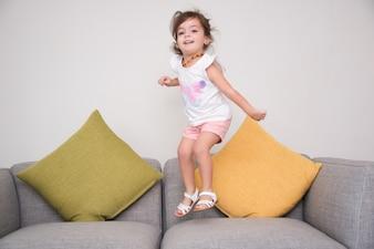 Carefree girl jumping on sofa