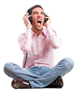 Casual man sitting on the floor and listening to music