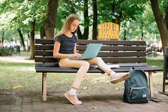 Casual teen studying with laptop