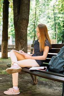 Casual youngster studying on bench in park