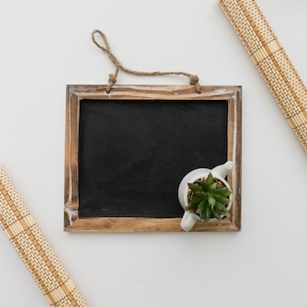 Chalkboard with flower pot on top