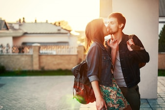 Charming couple with denim jackets kissing at sunset