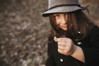 Charming girl holding tiny flower