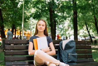 Charming student daydreaming on bench