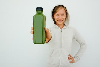 Веселая атлетическая женщина, рекомендующая спортивный напиток