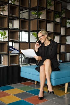 Cheerful businesswoman talking on phone in hotel