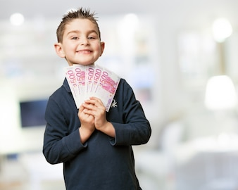 Cheerful child with a stack of bills